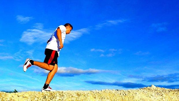 Mann joggt vor blauem Himmel