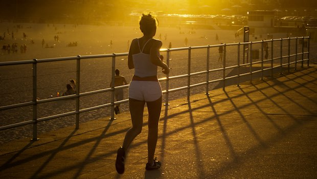 Joggerin am Strand mit Sonnenuntergang