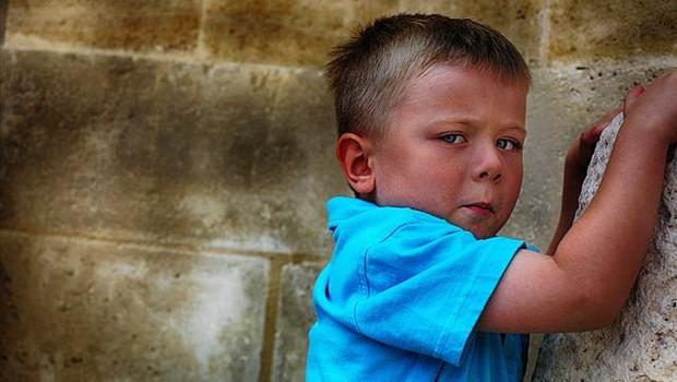 Junge vor Mauer