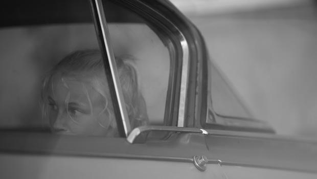 Kind blond sitzt im Auto