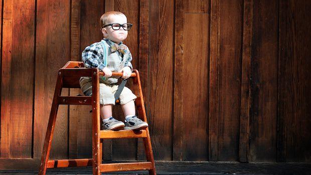 Kind im Hochstuhl mit Brille vor Holzwand