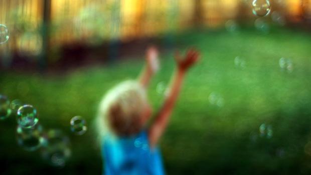 Kind faengt Seifenblasen