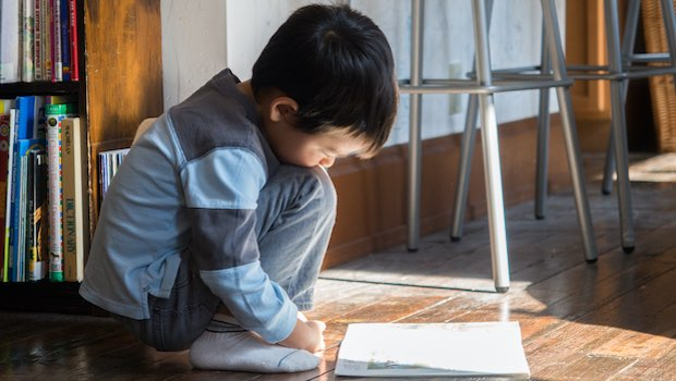 Kind lesen auf Holzboden