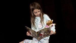 Mädchen liest Heft, mit Teddy im Arm