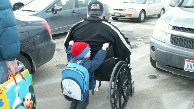 Kind schiebt Rollstuhl und Mann.