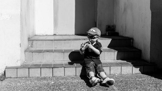 Kind sitzt auf Treppe, mit Tute