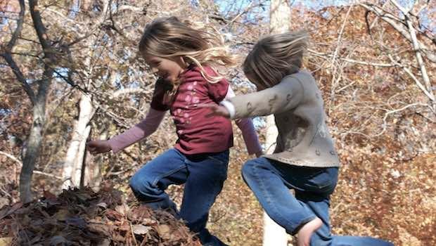 Kinder beim Sprung in Laubhaufen