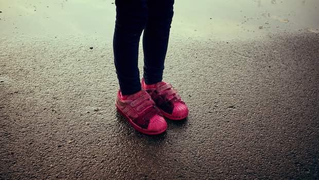 Kinderbeine mit pinken Schuhen Asphalt