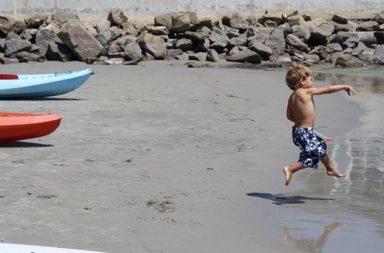 kleiner Junge, werfend am Strand