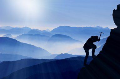 Mensch klettert Berg hoch im Dunkeln
