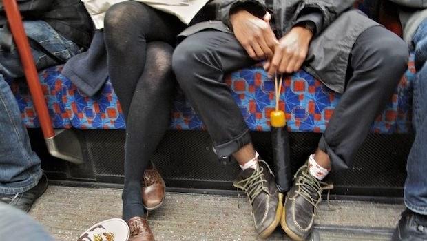 Mann sitzt breitbeinig in Bahn, Frau sitzt eng verknotet