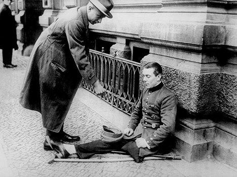 Mann in Uniform, amputiertes Bein, sitzt auf Bürgersteig, erhält Geld