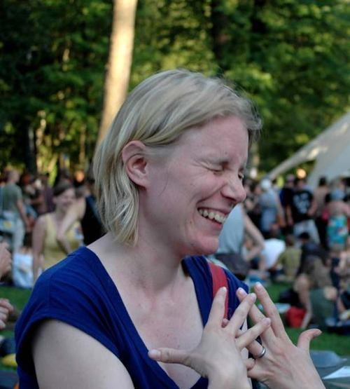 lachende blonde Frau in blauem T-Shirt