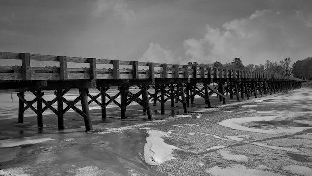 lange Brücke aus Holz unterhalb Meer