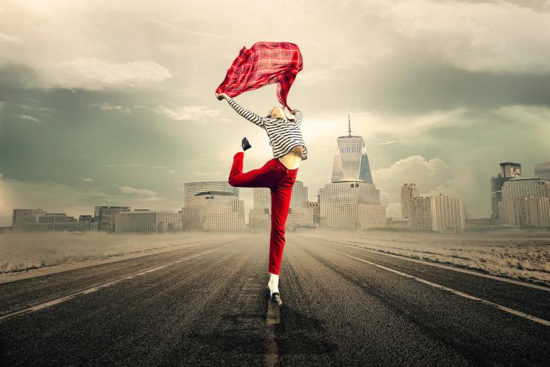Frau tanzt mit rotem Tuch vor grauer Stadt