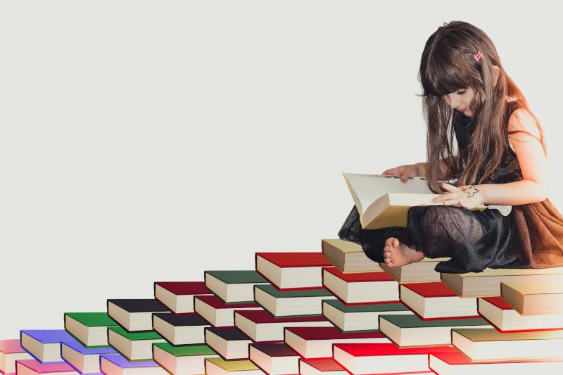 Mädchen sitzt auf Bücherstapel und liest.