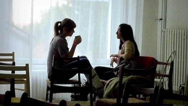 Mädchen Unterhaltung mit Tasse auf Sofa