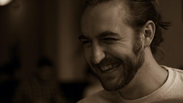 Männergesicht Zopf Bart lachend