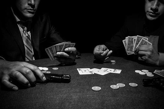 Zwei Männer mit Spielkarten, Chips und Pistole
