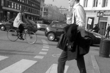 Mann in Anzug überquert Zebrastreifen