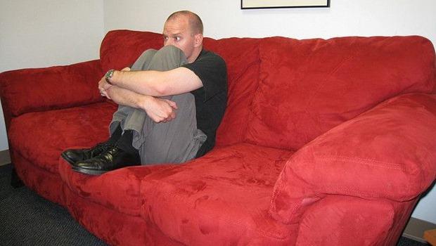 Mann sitzt auf rotem Sofa