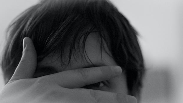 Mann versteckt sich hinter Augenschere