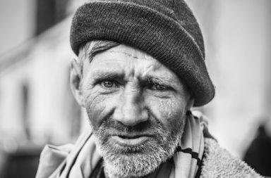 Mann mit Bart und Mütze obdachlos