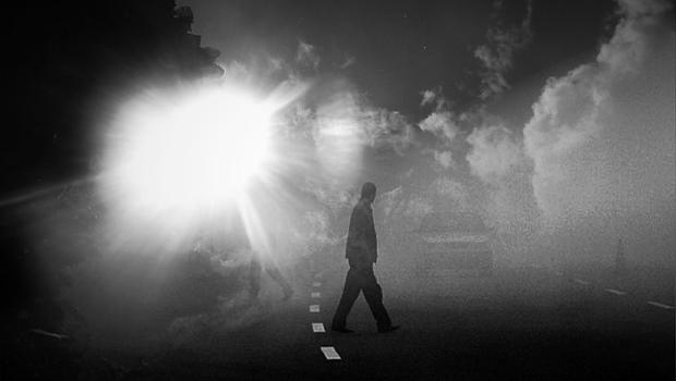 Mann im Nebel auf Straße, schwarzweiß