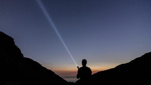 Mann leuchtet mit Lampe in den Nachthimmel