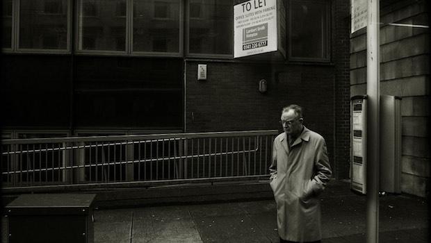 Mann mit Mantel und Brille schwarz weiß