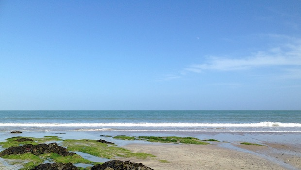 Meer ruhig Strand grüne Hügel