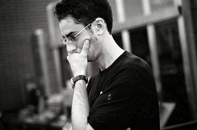 Mann mit Brille, linke Hand vorm Mund, schwarzweiß