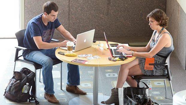 Mann und Frau an einem Tisch vor eigenem Laptop
