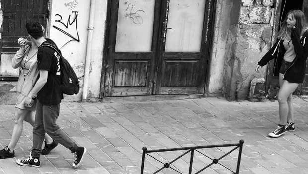 küssendes Paar auf Straße, dahinter Mädchen