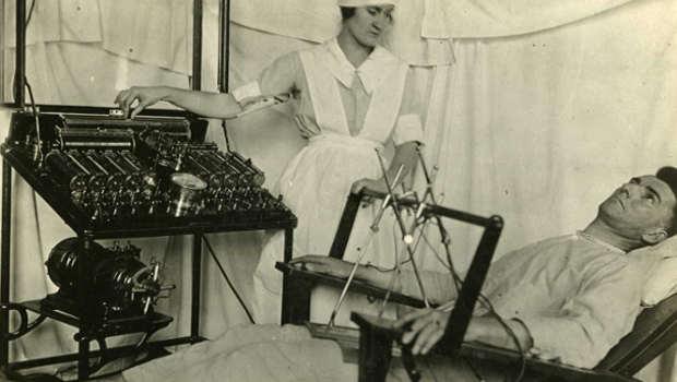 Patient auf Liege, Krankenschwester behandelt, Psychiatrie früher