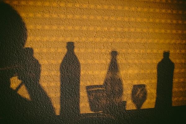 Getränkeflaschen, Gläser und fotografierende Person als Wandschatten