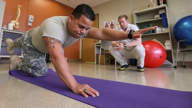 Mann macht kniend Physiotherapie, Mann in weiß hockt im Hintergrund, lila Matte