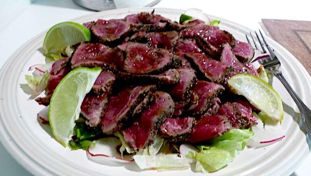 rotes Fleisch mit Salat und Limette auf Teller