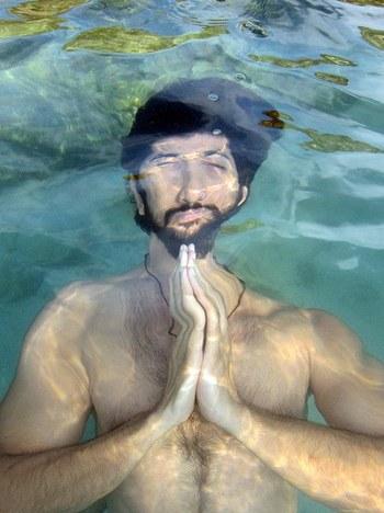 Mann mit Bart meditiert unter Wasser