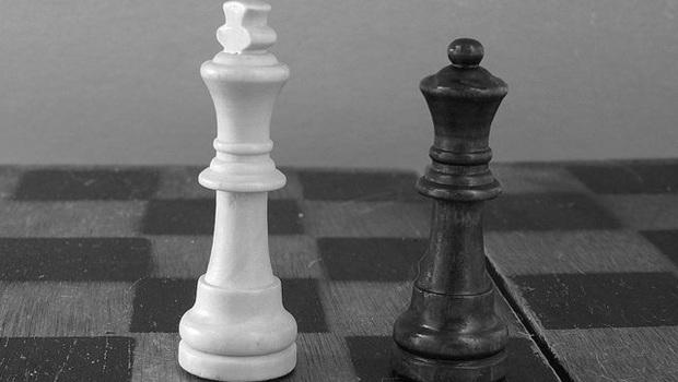 Weißer König, schwarze Dame auf Schachbrett