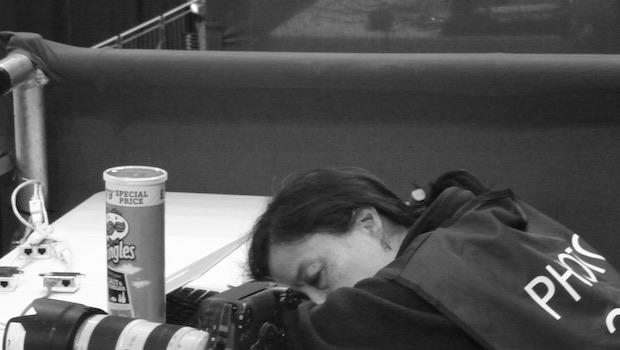 Frau schläft auf Tisch, daneben Kamera und Chips