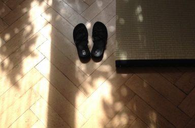 Schuhe auf Dielen neben Matratze