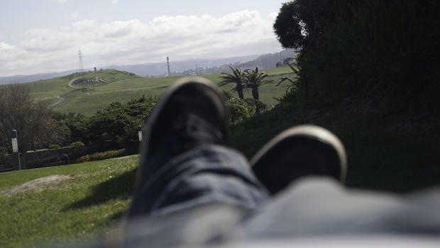 Beine mit Schuhen und Jeans ein Ausblick mit Palmen