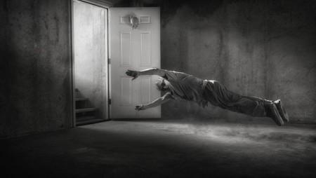 Mann schwebt durch Zimmer, schwarzweiß