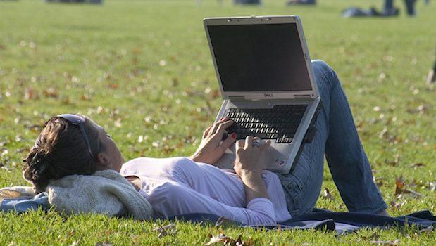 mit Notebook im Park arbeiten