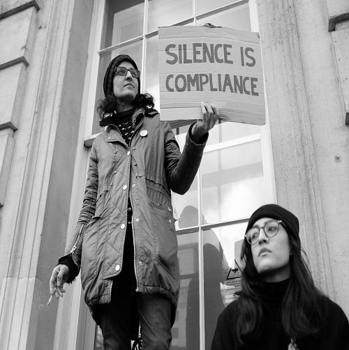 Zwei Frauen mit einem Schild und der Aufschrift: Silence is compliance