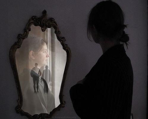 Frau schaut in alten Spiegel