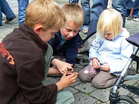 drei knieend spielende Kinder