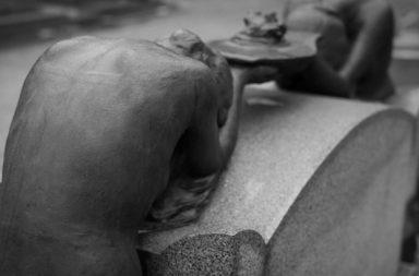 Statue gebeugt am Tisch Rückansicht