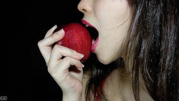 Frau mit roten Lippen beißt in Apfel